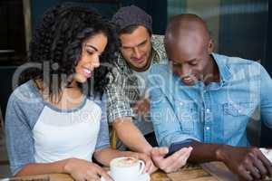 Friends using mobile phone in coffee shop