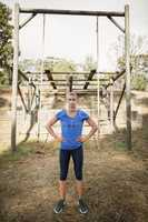 Portrait of woman standing with her hands on hip during obstacle course