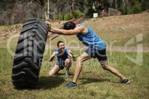 Fit man flipping a tire while trainer cheering during obstacle course