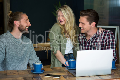 Cheerful male and female friends talking in coffee shop
