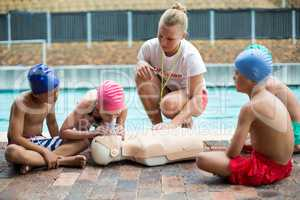 Lifeguard helping children during rescue training