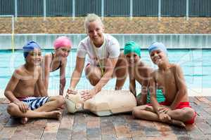 Happy children and instructor during rescue training at poolside