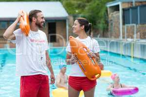 Lifeguards holding rescue cans at poolside