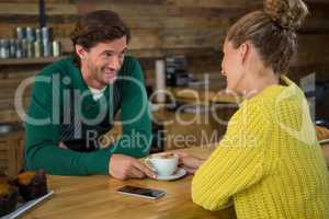 Barista serving coffee to woman in cafeteria