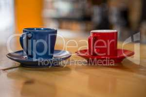 Coffee cups on wooden table in cafeteria