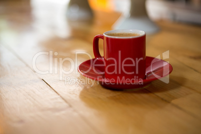 Red cup and saucer on table in coffee house