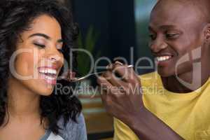 Loving man feeding dessert to woman in coffee shop