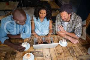 Friends using laptop at wooden table in coffee shop