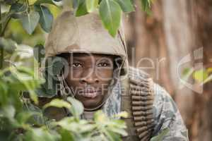 Military soldier hiding behind trees