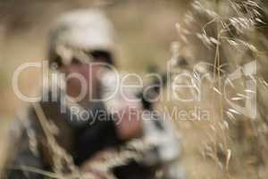 Military soldier hiding in grass while guarding