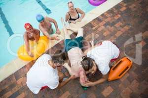 Friends looking at lifeguards saving unconscious senior man at poolside