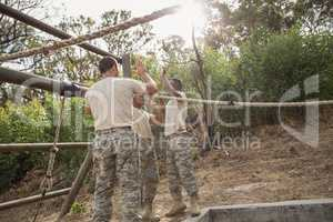 Young military soldiers giving after rope climbing during obstacle course