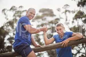 Man assisting woman to climb a hurdles during obstacle training