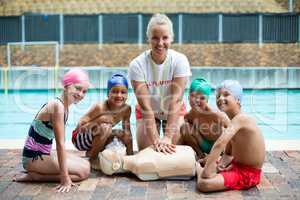 Cheerful female lifeguard and children during rescue training