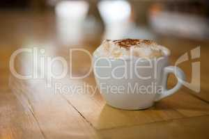 Coffee cup with creamy froth on wooden table