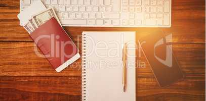 Pen on notepad next to keyboard and smartphone