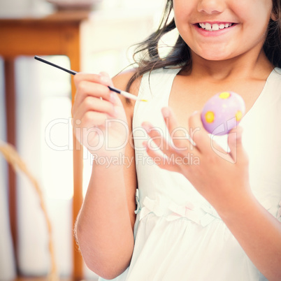 Cute girl painting easter eggs