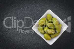 Large green olives in a white bowl