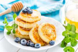Cottage cheese pancakes with honey and blueberry on white background, breakfast or lunch