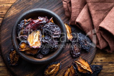 Prune, dried plums fruits on dark rustic wooden background
