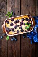 Blueberry cheesecake on dark wooden rustic backgroud, top view