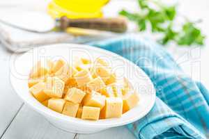 Cheese slices on plate, white background