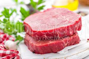 Raw, uncooked beef meat steaks on white wooden background