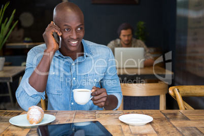 Man talking on phone while having coffee in coffee shop