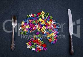 Cutlery and multicolored letters of wood on a black surface