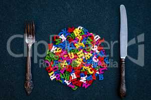 many wooden letters of the English alphabet among the fork and k