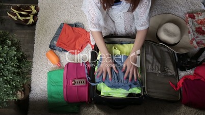 Female hands packing clothes into travel bag