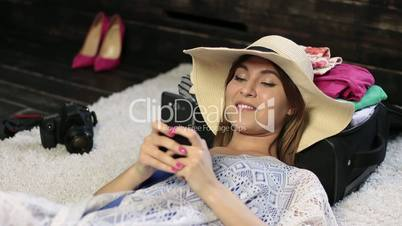 Woman lying on floor text messaging on cell phone