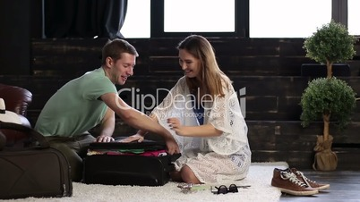 Couple trying to close their luggage together