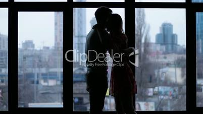 Silhouette of romantic couple embracing by window