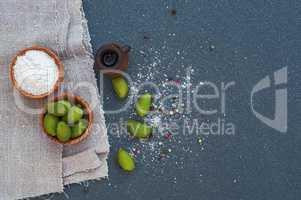 Olives and salt in wooden bowls, black surface