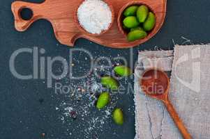 Large green olives and salt, wooden spoon