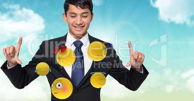 Digitally generated image of businessman looking at flying emojis against sky