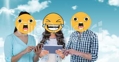Digitally generated image of friends faces covered with emoji using digital tablet and smart phone a