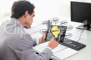 Businessman using tablet PC with various ideas on screen