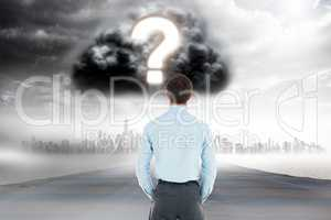 Digitally generated image of businessman looking at question mark in cloudy sky over city