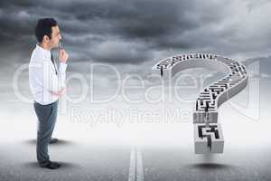 Digital composite image of businessman looking at maze question mark against sky