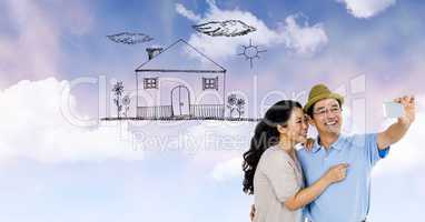 Happy couple taking selfie with house drawn on clouds