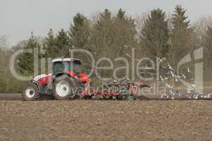 Agriculture ploughing tractor with seagulls.