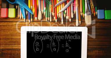 Overhead view of formula in digital tablet with color pencils and school supplies on wooden table