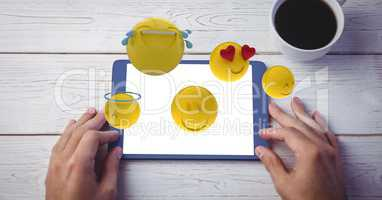 Digitally generated image of various emojis flying over hand using digital tablet at wooden table