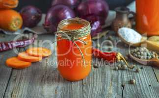 Juice from fresh vegetables in a glass jar on a table