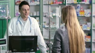 Young pharmacist counseling customer in pharmacy
