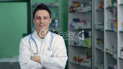 Pharmacist standing with crossed arms in pharmacy