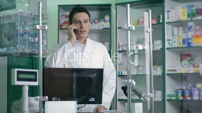 Male pharmacist communicating on phone in pharmacy