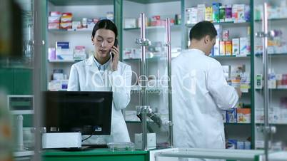Beautiful female pharmacist taking orders on phone